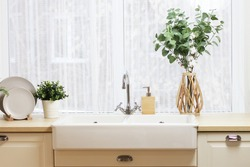 large kitchen sink by the window. a tray with plates, a vase with branches of eucalyptus and cotton, a flower pot with a flower on the countertop.