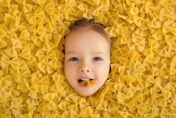 large pile of noodles in the form of a bow. The child eats pasta. Pasta made from durum wheat. The baby's face is surrounded by a large amount of macaroni. Beautiful baby blue eyes.