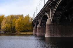large stone bridge with arches rises above  surface of  river. An old architectural structure. Beautiful autumn landscape.