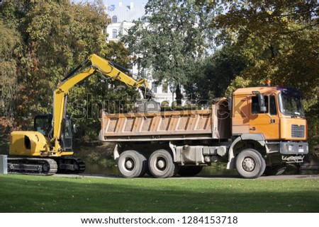 Latvia. Excavator loads trash in a park onto a truck #1284153718