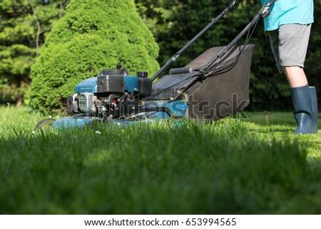 Lawn mower cutting grass  #653994565