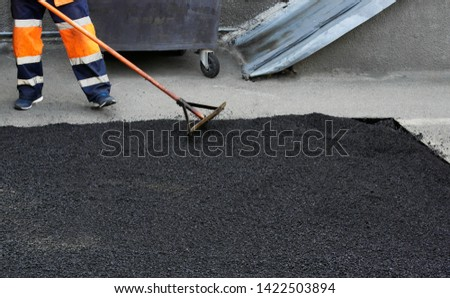 Laying asphalt, covering the pit, on the rubble. Workers carry in shovels, hot asphalt.closeup photo.