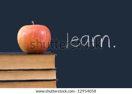 """learn"" written on blackboard with apple and books"