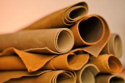 Leather brown assortment. Genuine leather rolls  set  brown tones on a blurred beige background.Leatherworking.Leather goods material.