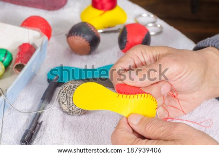 Leather craft, male hands sewing  traditional sport balls