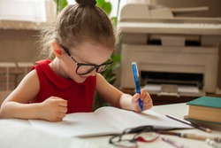 Left-handed. International left-handed day. Girl in glasses for sight. A girl writes in a notebook with her left hand. Education and science. Preschool education.