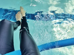 legs and feet of a woman bathing and relaxing in a pool of clear blue water with pool noodle - Female limbs soaking in a luxury spa resort jacuzzi and hydrotherapy facility with copy space