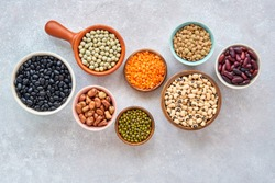 Legumes and beans assortment in different bowls on light stone background . Top view. Healthy vegan protein food.