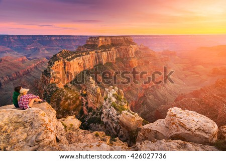(Lens flare effect) A group of people was sitting near the edge watching sunset at Grand Canyon National Park North Rim, USA. Grand Canyon National Park is one of the world's natural wonders