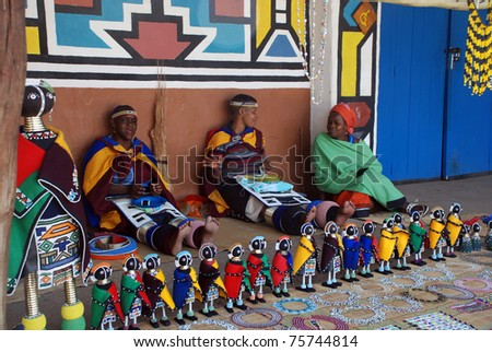 LESEDI  VILLAGE, SOUTH AFRICA - JANUARY 1: African ndebele women wearing traditional handmade accessories sell traditional dolls on January 01, 2008 in Lesedi African Lodge and Cultural village, South Africa