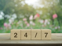 247 letter on block cubes on wooden table over blur pink flower and tree in garden, Business full time service concept