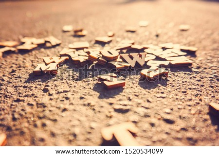 Letters fall on the asphalt, tinted photo of the English alphabet, learning and science.