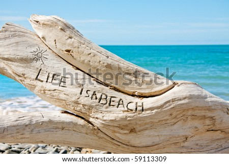 'Life is a beach' written on a log on a beautiful tropical beach