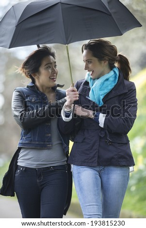 Lifestyle image of Caucasian and Asian women walking under an umbrella. Two happy female friends out having fun together.