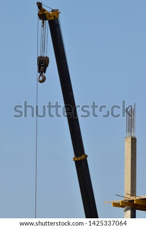 Lifting crane and concrete support at a construction site of a multistory building against a blue sky in the foothills of the North Caucasus                               #1425337064