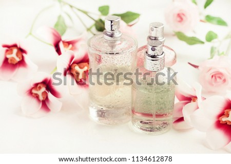 Light aroma perfume bottles wet with water drops surrounded by pink flowers on white bathroom shelf. Pastel colors toned. Feminine delicate scents product. #1134612878
