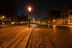 light from a lit street light in a city street at night. glowing lamp at night in the old town of prague in the czech republic