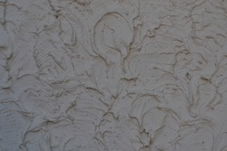 light putty on a cement wall is applied unevenly with pits and bumps