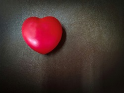 light red heart on dark brown synthetic leather textured with free copy space.