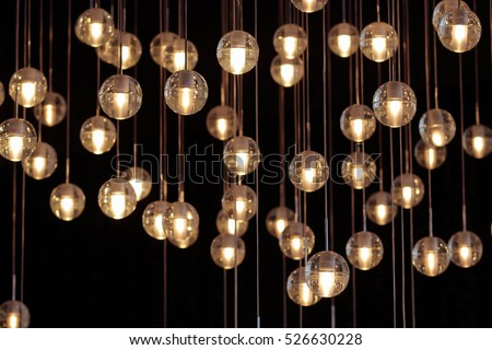 lighting balls on the chandelier in the lamplight,  light bulbs hanging from the ceiling, lamps on the dark background, selective focus, horizontal\r