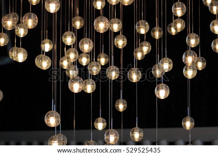 lighting balls on the chandelier in the lamplight,  light bulbs hanging from the ceiling, lamps on the dark background, selective focus, horizontal #529525435