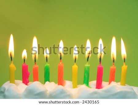 10 lit birthday candles in bright colors in white icing with green background. Horizontal image has copy space above. Candle colors are yellow, pink, orange and green. Candles are half melted down.