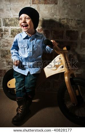 Little biker against a brick wall