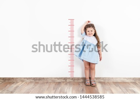 Little blond girl measuring height on white wall.