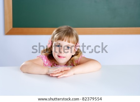 little blond girl student in classroom desk with blackboard