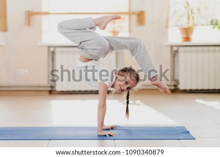 Little girl doing gymnastic exercises #1090340879