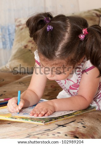 little girl drawing with pencils at home