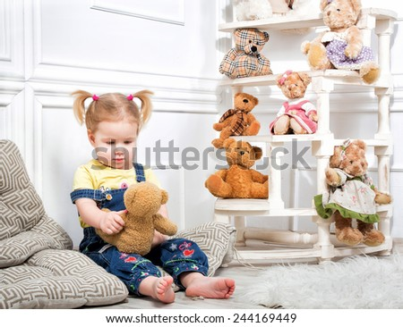 Little girl holding a teddy bear. Little girl in denim overalls sitting on cushions surrounded by toys