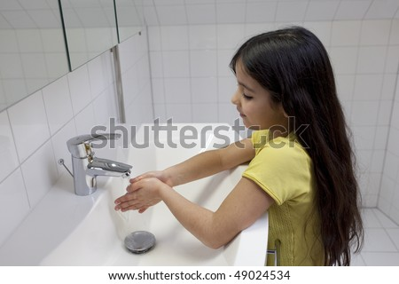 Little girl is washing her hands in the bathroom