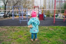little girl on an empty closed playground closed quarantine of the corona virus, isolation, covid 19