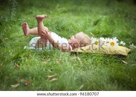 little girl on soft pillow in fresh spring grass