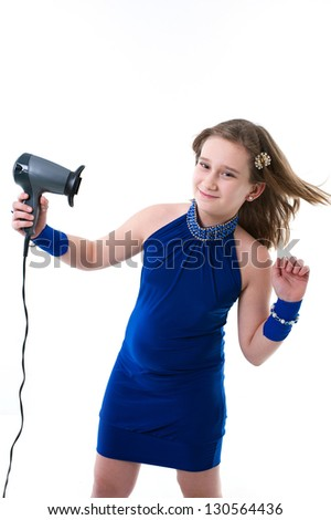 little girl posing with hair dryer isolated on white. smiling little girl in blue dress. portrait of a happy little girl playing, isolated on white background.