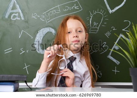 Little girl schoolgirl with glasses sitting at table        smile
