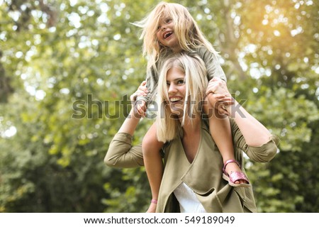Little girl sitting on her mother's shoulders. ストックフォト ©