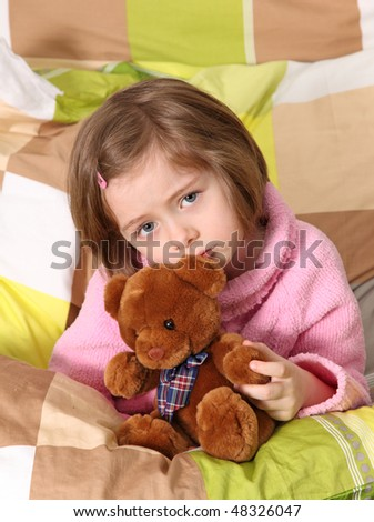 Little girl sitting sick in bed
