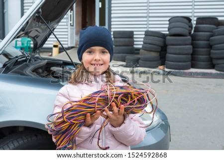 Little girl with a wire in her hands works in a car service. Repair service.