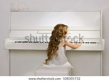 little girl with blond long curl hair in a white dress playing white piano