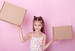Little girl with two parcel box isolated on pink.  Little girl playing with  boxes.  Beautiful childe with cardboard boxes.