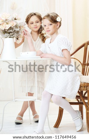 2 little girls in white dresses sitting in cafe and looking at you