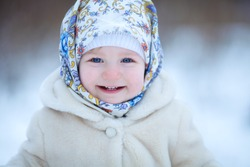 Little Russian girl in a white coat. Winter landscape. Image with selective focus and toning.