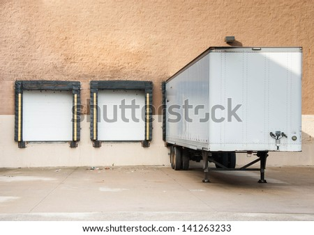 Loading docks and the semi truck trailer transferring cargo in the industrial area or for departmental store. Where is the cargo?