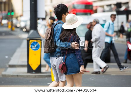 London, UK - August 24, 2016: Young Chinese couple crossing the Piccadilly circus junction - Shutterstock ID 744310534