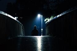 lonely man sitting on a bridge in the rain alone under a streetlight