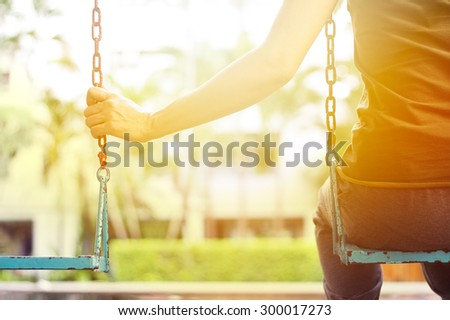 Lonely woman missing her boyfriend while swinging in the park villa in the morning