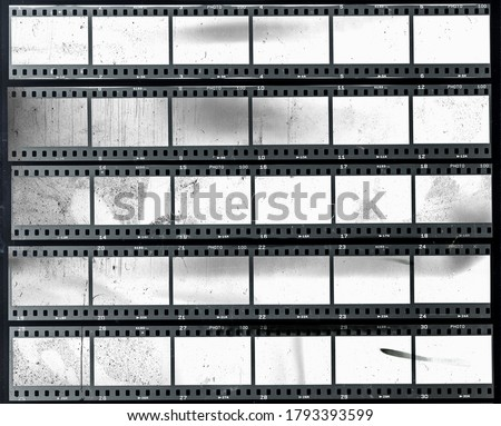 Photo of  5 long and empty or blank 35mm filmstrips, black and white film material behind real foil, cool retro photo placeholder.