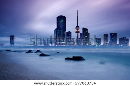 long exposure of kuwait city skyline during blue hour  #597060734